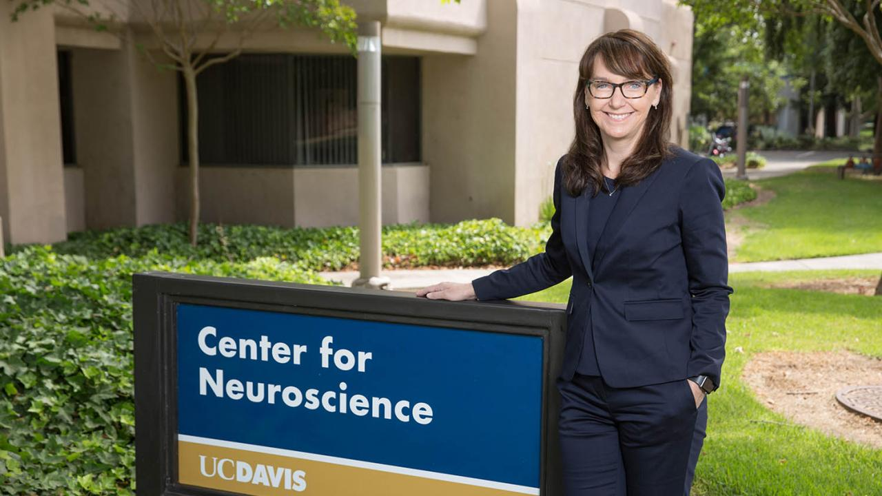 picture of kim next to the center for neuroscience sign