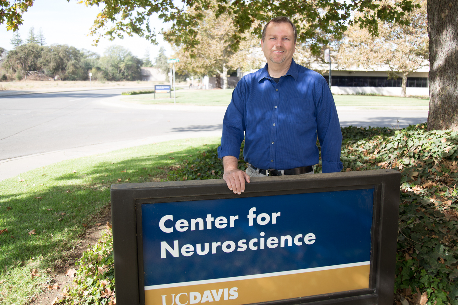 Picture of Marty in front of the center for neuroscience sign