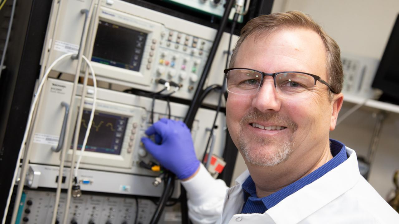 Picture of Marty in lab gear adjusting equipment